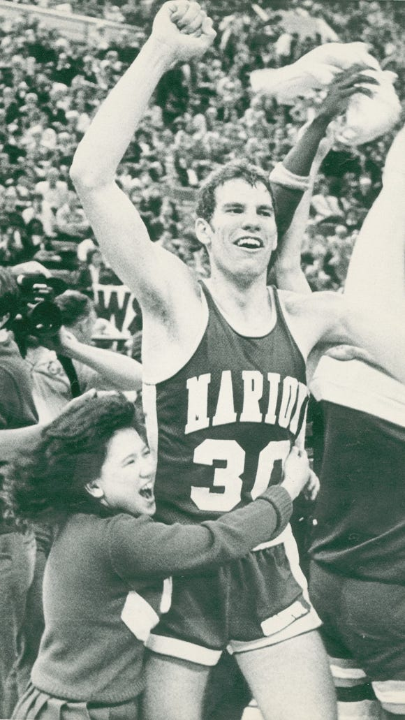 Marion center Jay Teagle gets a hug from a Marion cheerleader after Marion won the 1985 Indiana boys state basketball championship.  Marion defeated Richmond 74-67.  March 23, 1985 AP file photo