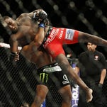 Daniel Cormier lifts Anthony Johnson during their light heavyweight title bout at UFC 187 on May 23 in Las Vegas.