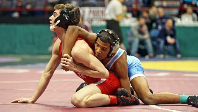 Alex Delacruz of Ossining, right, battles Richie Burke of Ithaca in a 126 pound semifinal match at the New York State Wrestling Championships at the Times Union Center in Albany March 1, 2014. Delacruz defeated Burke 9-1.