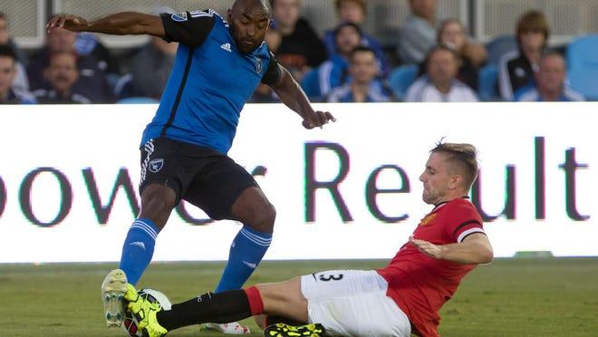 Manchester United defender Luke Shaw slide tackles Earthquakes defender Marvell Wynne during the first half.