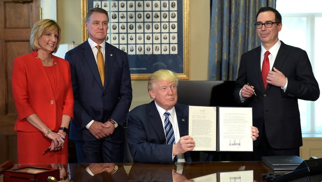 President Trump shows a memorandum he signed on Orderly Liquidation Authority at the Treasury Department on Friday, April 21, 2017. From left are Rep. Claudia Tenney, Sen. David Perdue, and Treasury Secretary Steven Mnuchin.