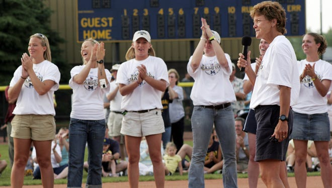Michigan softball coach Carol Hutchins, holding microphone at right, listens to applause while speaking at a rally celebrating her team's win in the NCAA Women's College World Series, at Alumni Field in Ann Arbor, Mich., Thursday, June 9, 2005.