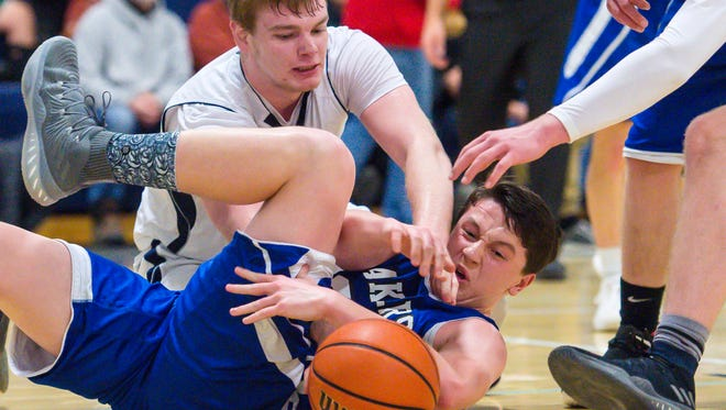 Mt. Mansfield Union's Mark Howland, left, and Colchester's Conroy O'Donnell go after a loose ball in Jericho on Thursday, January 11, 2018.