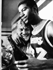 "Los Angeles Lakers Earvin ""Magic"" Johnson hugs team owner Jerry Buss in the locker room after they won the 1980 NBA championship from the 76ers in Philadelphia."