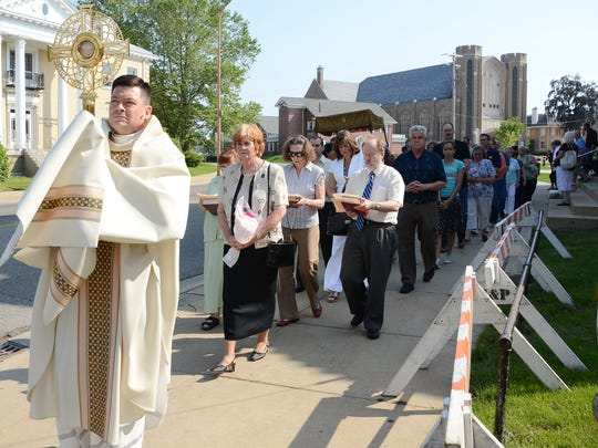 The Rev. John Fleckenstein, pastor of St. Philip Catholic Church, followed by singing and praying church members, proceeds along Capital Avenue Northeast in 2012.