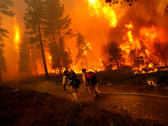 Firefighters head up the hill during the Angora fire Tuesday night, June 26, 2007, South Lake Tahoe, Calif. Hundreds of firefighters on Wednesday tried to tame a blaze near California's Lake Tahoe resort area on two fronts, facing the prospect of losing hundreds more homes if they failed to hold both of them.