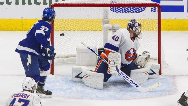 Tampa Bay Lightning's Yanni Gourde (37) watches the puck go in past New York Islanders goalie Semyon Varlamov (40) on Wednesday in Edmonton, Alberta.