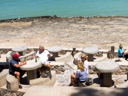 Vacacionistas disfrutan de mariscos y bebidas frente
