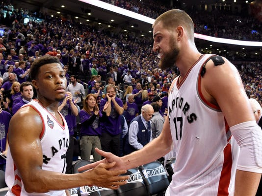 Toronto Raptors' Kyle Lowry (7) and Jonas Valanciunas (17) slap skin after taking down the Indiana Pacers in game two, round one NBA basketball playoff action in Toronto on Monday, April 18, 2016. (Frank Gunn/The Canadian Press via AP) MANDATORY CREDIT