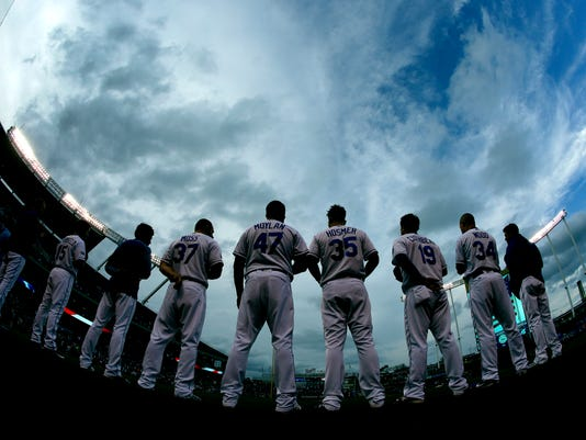 Players for the Kansas City Royals stand for the national anthem before a baseball game against the San Francisco Giants on Wednesday, April 19, 2017, in Kansas City, Mo. (AP Photo/Charlie Riedel)