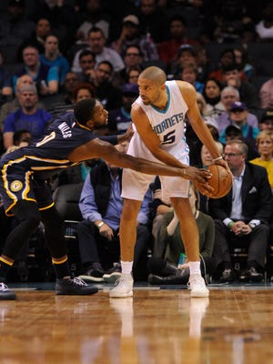 Charlotte Hornets guard forward Nicolas Batum (5) looks to pass the ball as Indiana Pacers guard C.J. Miles (0) looks to steal it during the first half of the game at the Spectrum Center.
