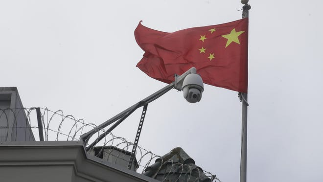 The flag of China flies behind a security camera over the Chinese Consulate in San Francisco on Thursday. The consulate is harboring a Chinese researcher who the FBI says lied about her military background.