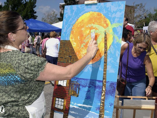 The 28th annual Riverwalk Arts Festival will take place this weekend in downtown Milton. In this photo from a previous festival, artist Carla D. Milam creates a painting using a putty knife and acrylic paint.