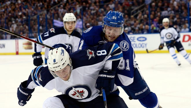 Tampa Bay Lightning center Steven Stamkos (91) and Winnipeg Jets defenseman Jacob Trouba (8) fight to control the puck during the second period at Amalie Arena.