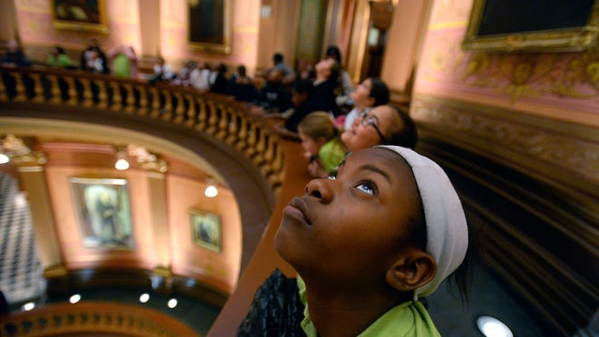 Students from Burton Glen Academy (Burton) look at the huge paintings above them in the Rotunda a at the Capitol during a tour of the building in Lansing Monday.