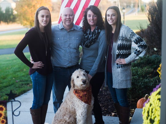 Rick Phillips, with his wife, April Phillips, and twins Brianna and Amber, right, and their labradoodle, Tucker, pictured at their home near Gettysburg. Rick suffered a brain injury when his police car crashed into a tractor-trailer during a high-speed chase in 2010.