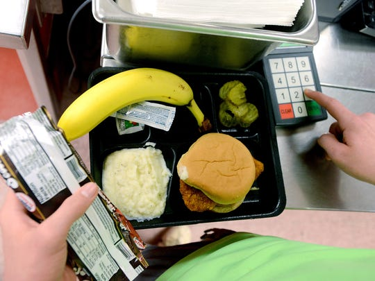 A student pays for his school lunch in the  Erwin Middle School cafeteria in this file photo from 2015.
