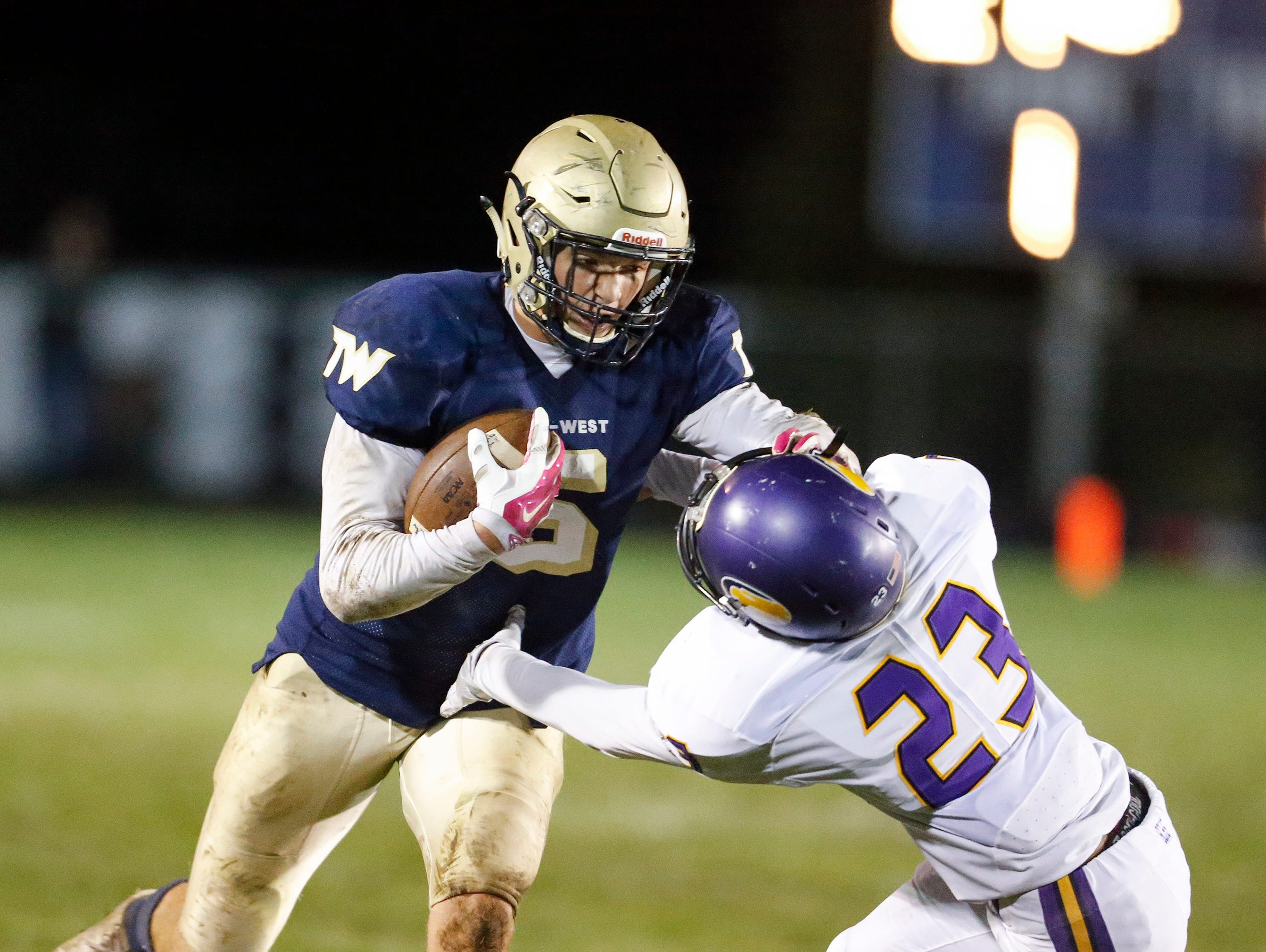 Tri-West's Peyton Hendershot (5) stiff arms Guerin Catholic's Shawn Balance (23) during their sectional game at Tri-West.