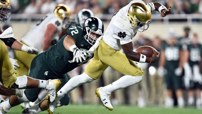 Sep 23, 2017; East Lansing, MI, USA; Notre Dame Fighting Irish quarterback Brandon Wimbush (7) runs for a touchdown as Michigan State Spartans defensive tackle Mike Panasiuk (72) attempts to tackle in the first quarter at Spartan Stadium. Mandatory Credit: Matt Cashore-USA TODAY Sports