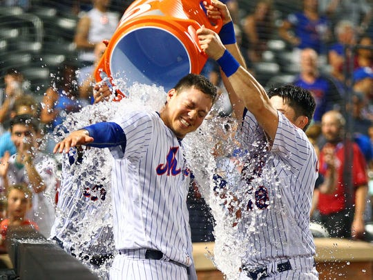July 22: Wilmer Flores, left, gets doused after his