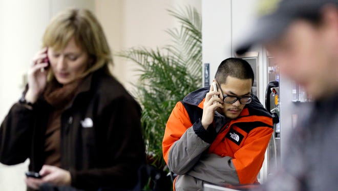Passengers talk on their phones at Chicago's Midway Airport.