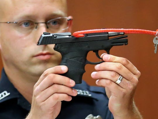 Sanford police officer Timothy Smith holds up the gun