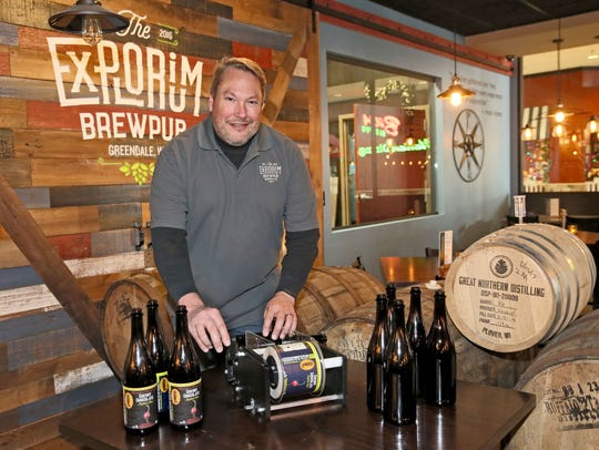 Mike Doble, owner of The Explorium Brew Pub in Greendale, puts labels on bottles for his Black Friday brew, a bourbon barrel-aged Cherry Chocolate Imperial Stout.
