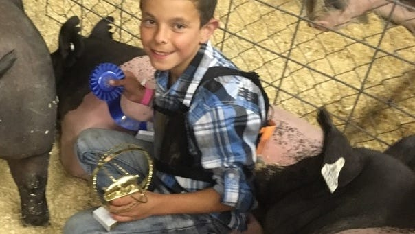 Blake Kroll with his blue ribbon and showmanship award after the Kewaunee County Fair auction.