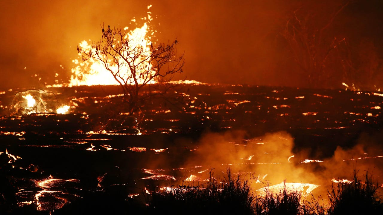 Fast-moving lava crossed a road and isolated about 40 homes Friday in a rural subdivision below Hawaii's Kilauea volcano, forcing at least four people to be evacuated by county and National Guard helicopters. (May 19)