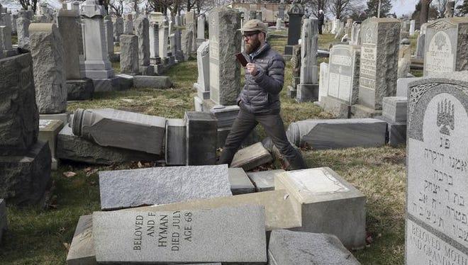 Rabbi Joshua Bolton of the University of Pennsylvania's Hillel Center surveys damaged headstones at Mount Carmel Cemetery.