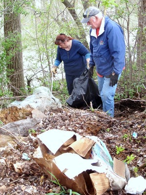 Corning Town Supervisor Kim Feehan, left, and volunteer Tim Maney pick up trash Saturday at a Chemung River public access site.