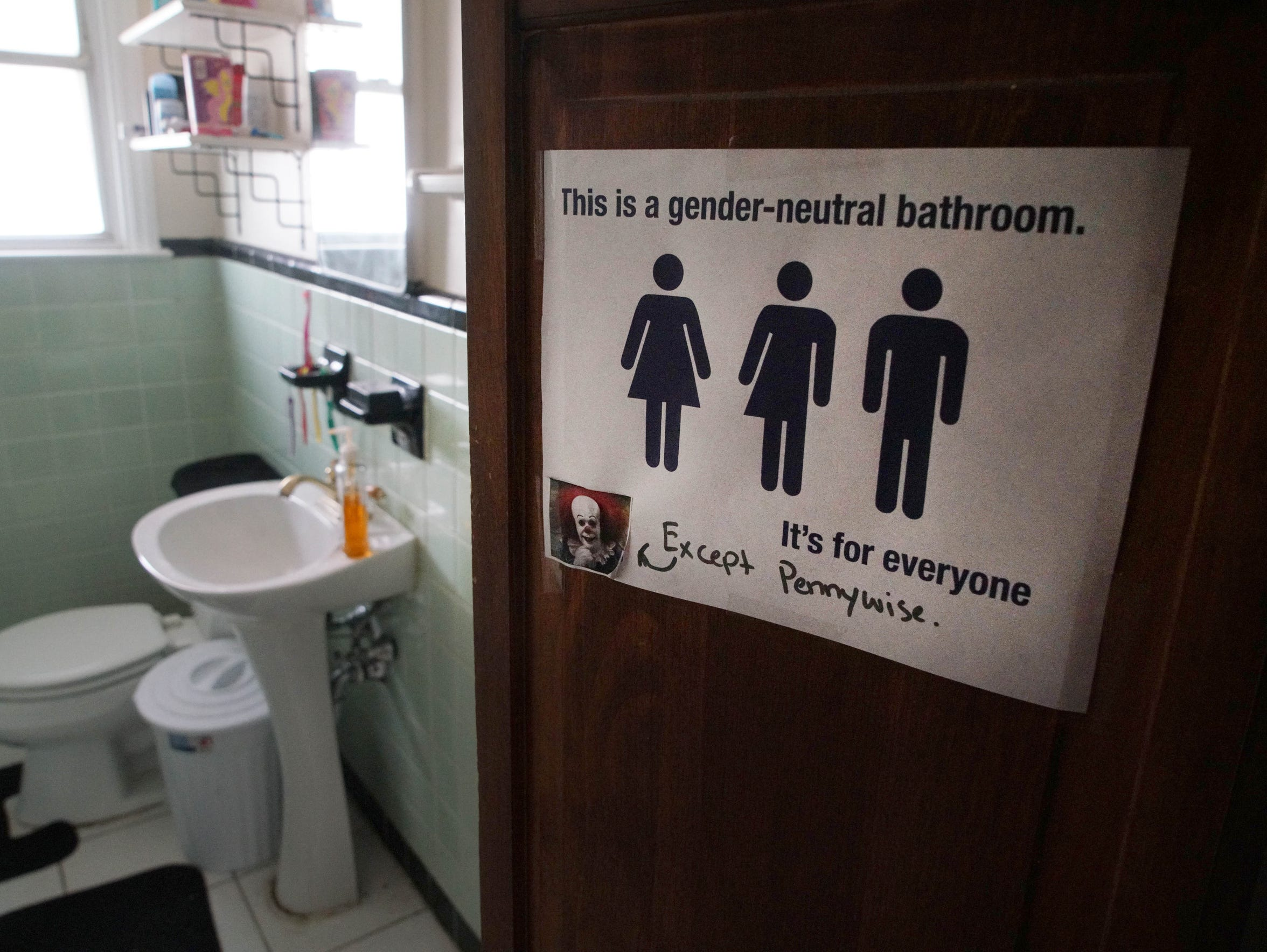 A transgender friendly sign hangs outside of the master