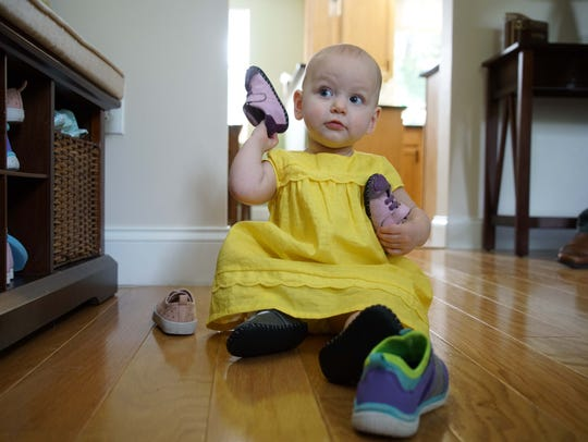 Cate Lawrence plays with shoes from a nearby storage area. She turned 1 on Saturday.