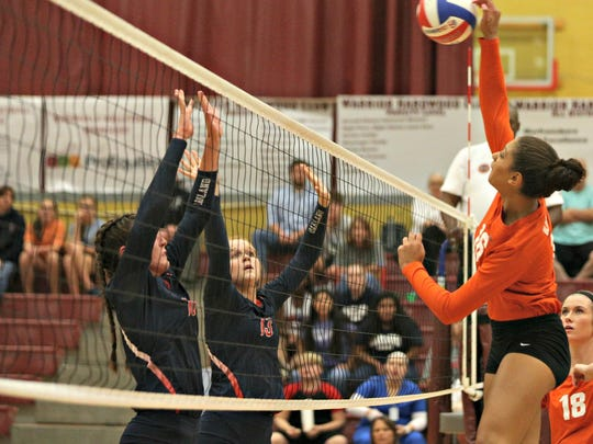 Blackman's Hailey Ivy gets high over the net on a kill attempt as Oakland's Jessica Paden (left) and Kara Nelms prepare to block.