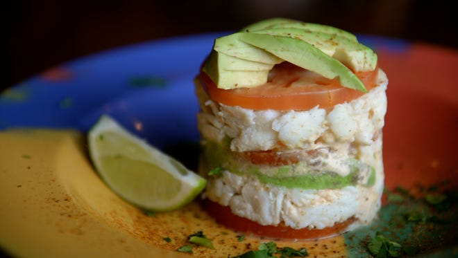 Dos Locos' crab mountain — lump crab meat, sliced tomato, sliced avocado and spicy chipotle sauce layered and served with fresh cilantro and lime.