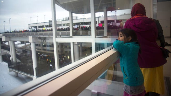 Emily Wang of Canton and her daughter watch the protests at Detroit Metropolitan Airport.