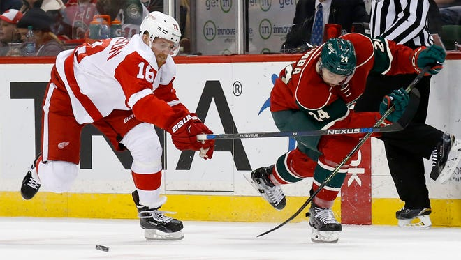 Minnesota Wild defenseman Matt Dumba (24) passes the puck in front of Detroit Red Wings center Joakim Andersson (18), of Sweden, during the second period of an NHL hockey game in St. Paul, Minn., Monday, Dec. 28, 2015.
