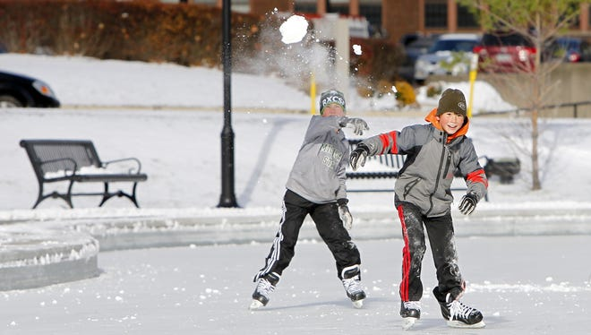 Trevor August, right, tries to outrun a snowball from his twin brother, Owen, both 11 and of Mendon, during opening day at the Martin Luther King Jr. Memorial Park Ice Rink in Rochester in 2013.