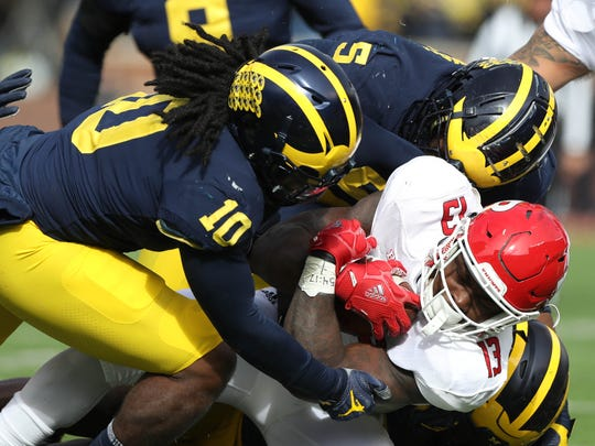 Michigan's Devin Bush (10) and Aubrey Solomon (5) help tackle Rutgers' Gus Edwards in the first quarter Saturday, Oct. 28, 2017 at Michigan Stadium.