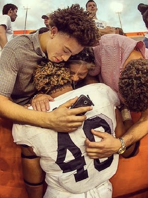Brothers Henry and Stephen Jackson hug their brother, Edwin, after Georgia Southern defeated Florida 26-20 in 2013.