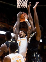 Tennessee guard Lamonte Turner (1) attempts a shot in between Vanderbilt center Djery Baptiste (12) and Vanderbilt forward Clevon Brown (15) during Tennessee's home basketball game against Vanderbilt at Thompson-Boling Arena on Tuesday, January 23, 2018.