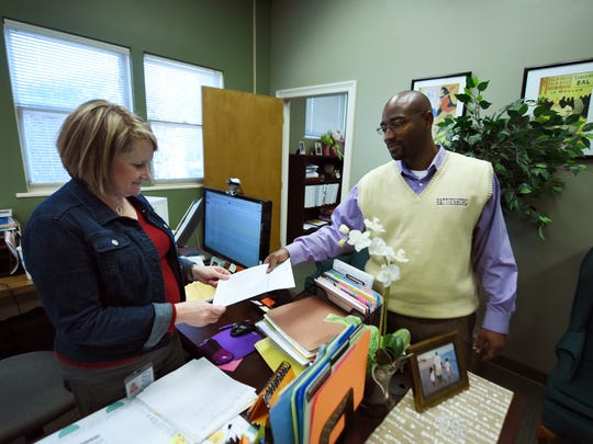 Hattiesburg Public School District Superintendent Robert Williams speaks with Nancy McGee, federal programs specialist, in the HPSD office.