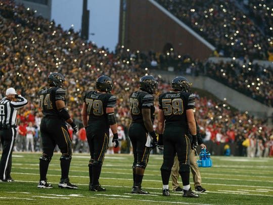 Members of the Iowa offensive line wait for the play