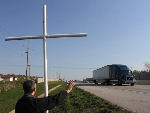 Rob Wood holds a 10-foot cross made of PVC pipe and waves at traffic on U.S. 65 on Good Friday, April 18, 2014.
