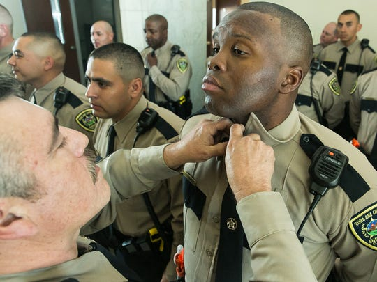 Cadet Antwian Cummings gets his necktie adjusted by Deputy Manny Maynes on Thursday, Feb. 25, 2016, at Doña Ana Community College auditorium before the DASO's 21st Law Enforcement Academy Graduation Ceremony.