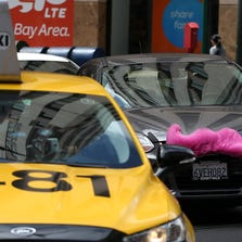 SAN FRANCISCO, CA - JUNE 12: A Lyft car drives next to a taxi on June 12, 2014 in San Francisco, California. The California Public Utilities Commission is cracking down on ride sharing companies like Lyft, Uber and Sidecar by issuing a warning that they could lose their ability to operate within the state if they are caught dropping off or picking up passengers at airports in California. (Photo by Justin Sullivan/Getty Images)