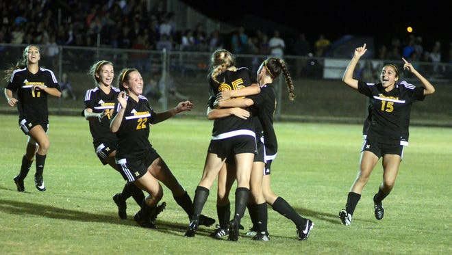 The Hendersonville High girls soccer team celebrates after junior Sydney Cason (25) scored the game-tying goal in the second half of Saturday evening's Class AAA sectional match at Independence. Cason scored two goals in the Lady Commandos' 3-1 victory, sending the team to the Class AAA State Tournament.