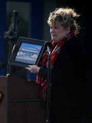 Jamie Highsmith holds up a photo of the new tennis complex at Lake View High School during a small ceremony dedicating the complex in honor of tennis Coach Brandon Clark Monday, Nov. 21, 2016.
