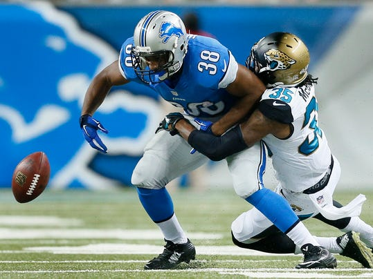 Jacksonville Jaguars cornerback Demetrius McCray (35) forces  Detroit Lions running back George Winn (38) to fumble in the second half of a preseason NFL football game at Ford Field in Detroit, Friday, Aug. 22, 2014. (AP Photo/Rick Osentoski)