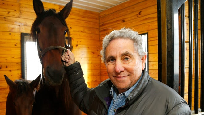 Jeffrey Gural, owner of Allerage Farm in Sayre, Pennsylvania, poses with a mare and foal in his barn Oct. 30.